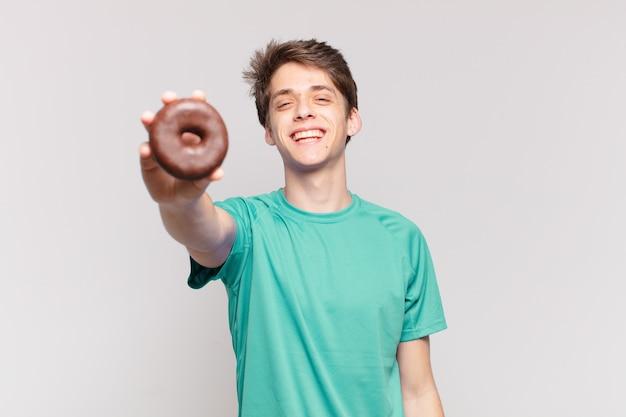 Młody nastolatek mężczyzna szczęśliwy wyraz twarzy i trzymający pączek