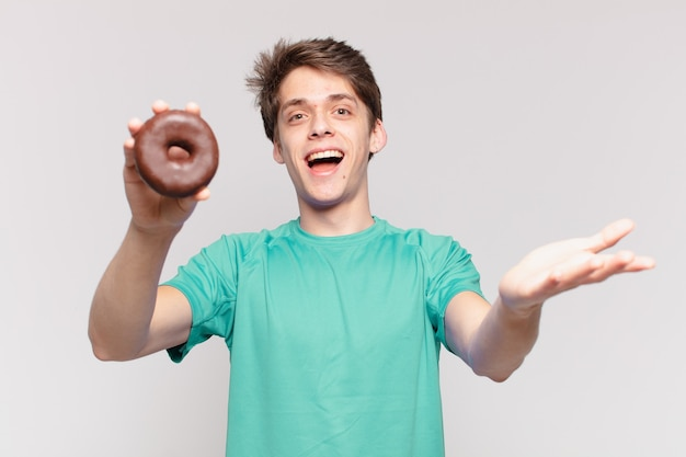 Młody nastolatek mężczyzna zaskoczony wyrazem twarzy i trzymający pączek