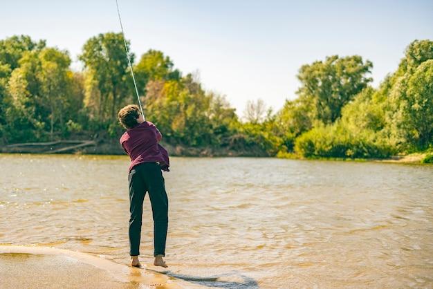 Młody nastolatek rybak w dorywczo łowienie ryb na brzegu rzeki z prętem w letni dzień