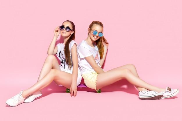 Młody nastolatek siedzi na deskorolce