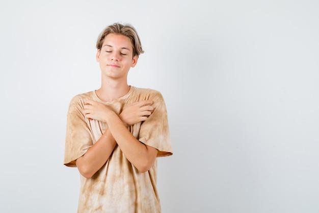 Młody nastolatek trzymający skrzyżowane ręce na piersi, zamykający oczy w t-shircie i patrzący spokojnie. przedni widok.