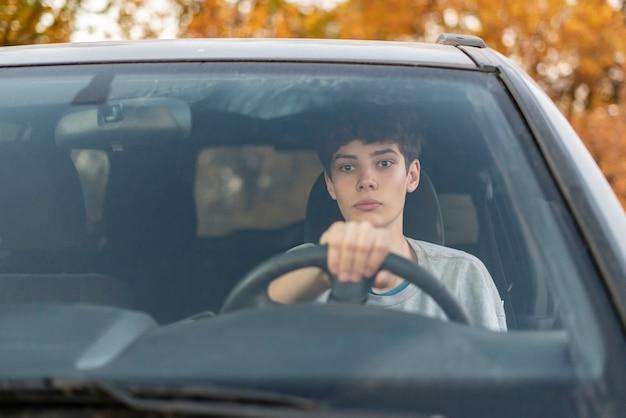Młody nastolatek uczy się prowadzić samochód f