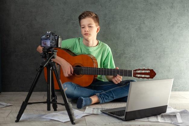 Młody nastolatek videobloger uczy się grać na gitarze online w salonie, odpoczywając w domu.