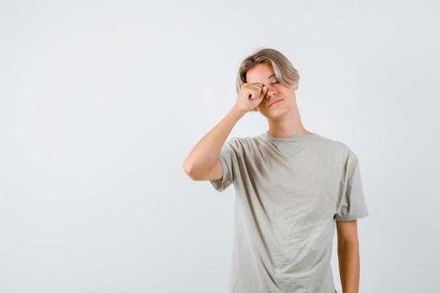 Młody nastolatek w koszulce pociera oczy i wygląda na zaspanego