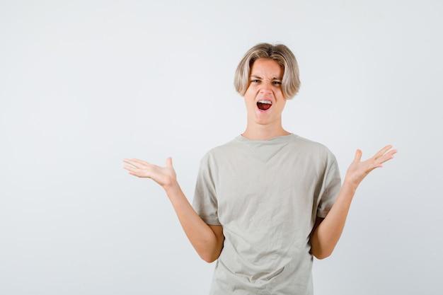 Młody nastolatek w koszulce pokazujący bezradny gest, krzycząc i patrząc energicznie
