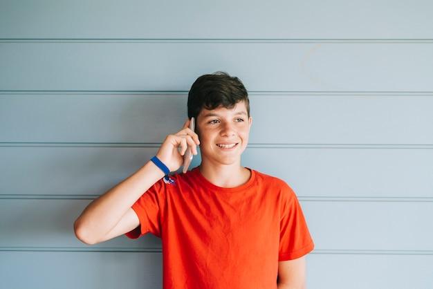 Młody nastolatek z czerwoną koszulki pozycją przeciw ścianie podczas gdy używać telefon