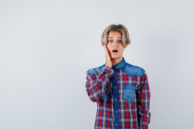 Młody nastolatek z ręką na policzku w kraciastej koszuli i wyglądający na zaskoczonego