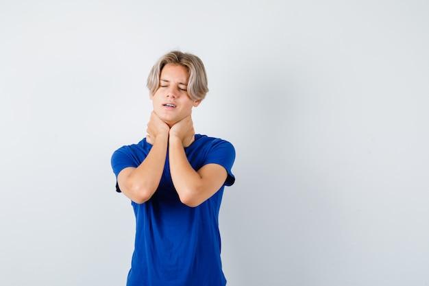 Młody nastoletni chłopak cierpiący na ból gardła w niebieskiej koszulce i wyglądający na zaniepokojonego. przedni widok.