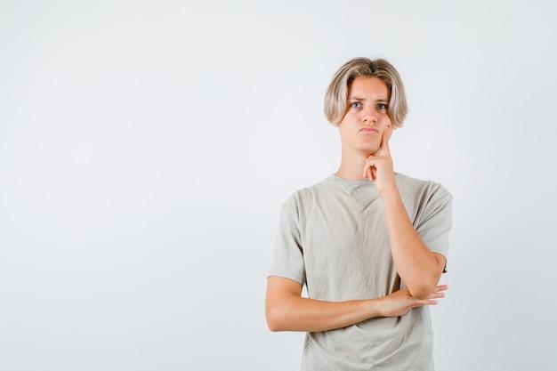 Młody nastoletni chłopak naciskający palec na policzek