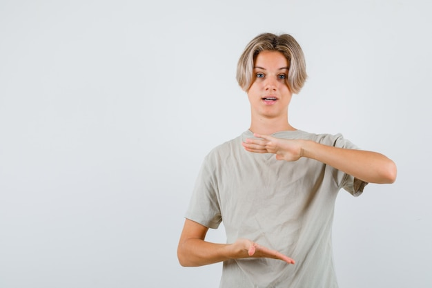 Młody nastoletni chłopak pokazujący duży znak w koszulce i patrzący na zdziwionego