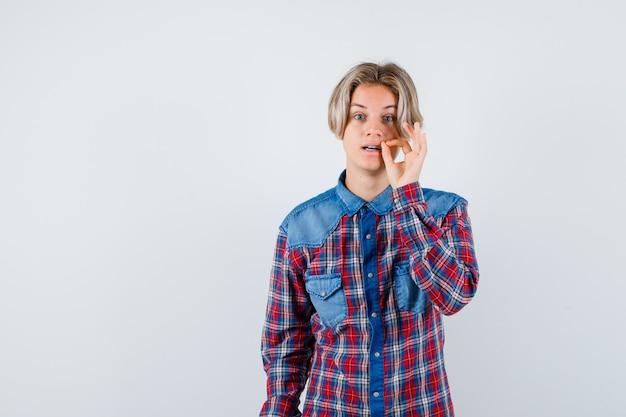 Młody nastoletni chłopak pokazujący gest suwaka w kraciastej koszuli i patrzący ostrożnie