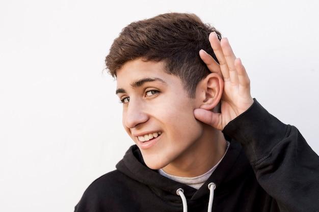 Młody nastoletni chłopak próbuje słuchać coś przeciw białemu tłu