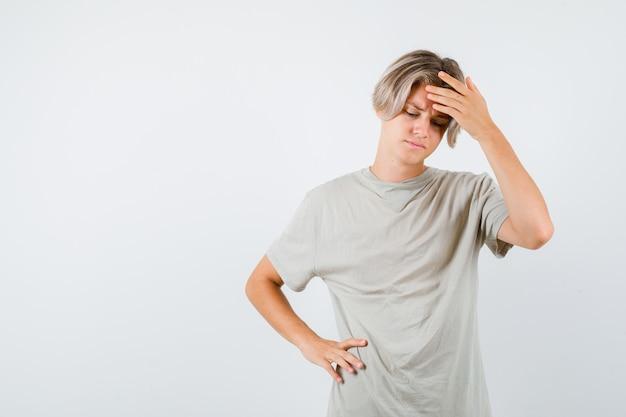 Młody nastoletni chłopak w koszulce cierpiący na ból głowy i wyglądający na przygnębionego