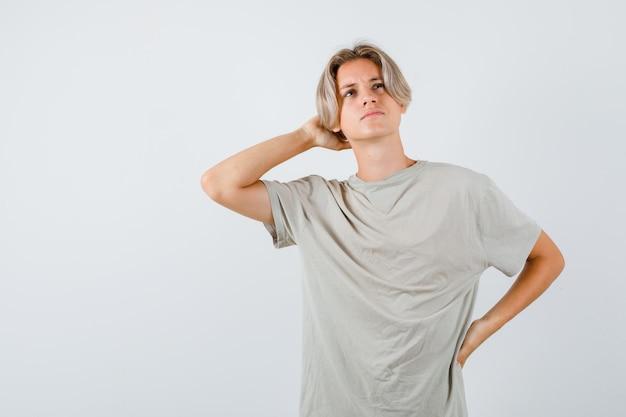Młody nastoletni chłopak w koszulce trzymający rękę za głową