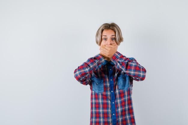 Młody nastoletni chłopak w kraciastej koszuli z rękami na ustach i wyglądający na wzburzony