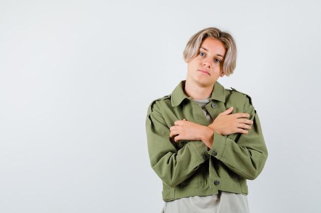 Młody nastoletni chłopak w zielonej kurtce ze skrzyżowanymi rękami na klatce piersiowej i patrzący z nadzieją