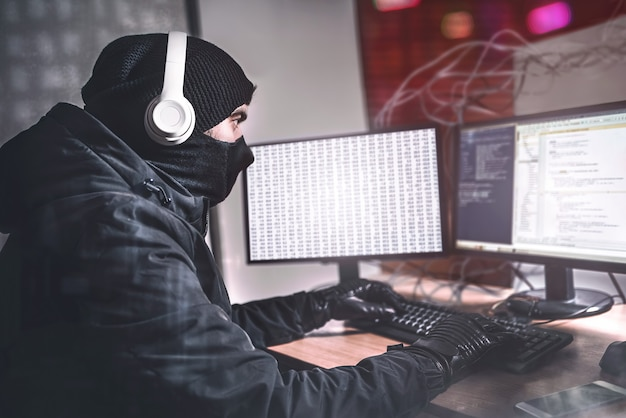 Młody nastoletni haker za pomocą swojego komputera w celu zorganizowania ataku złośliwego oprogramowania na skalę globalną. jest w podziemnym sekretnym miejscu otoczonym wyświetlaczami i kablami.