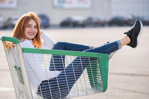 Młody nastoletni szczęśliwy dziewczyny obsiadanie w supermarketa wózek na zakupy outdoors.