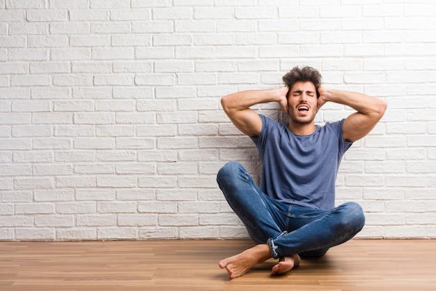 Młody naturalny człowiek siedzi na drewnianej podłodze szalony i zdesperowany, krzycząc poza kontrolą