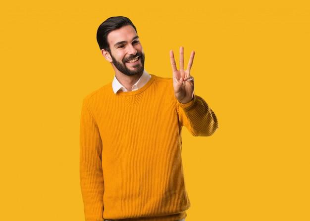 Młody naturalny mężczyzna pokazuje liczbę trzy