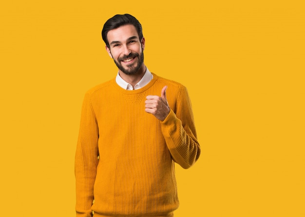 Młody naturalny mężczyzna uśmiecha się kciuk up i podnosi