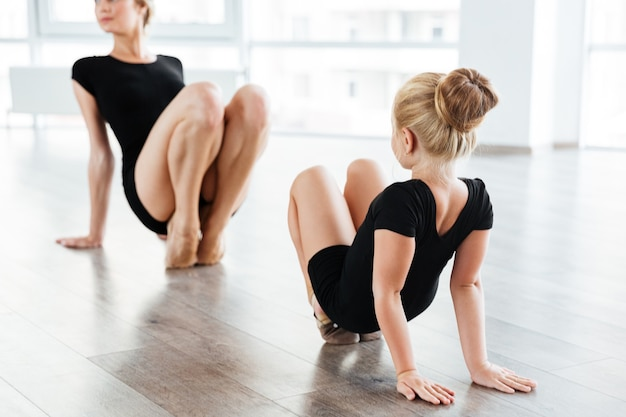 Młody nauczyciel baletu i jej mały uczeń w klasie baletu