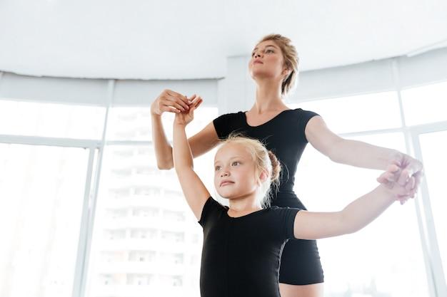 Młody nauczyciel baletu i jej mały uczeń w studio tańca