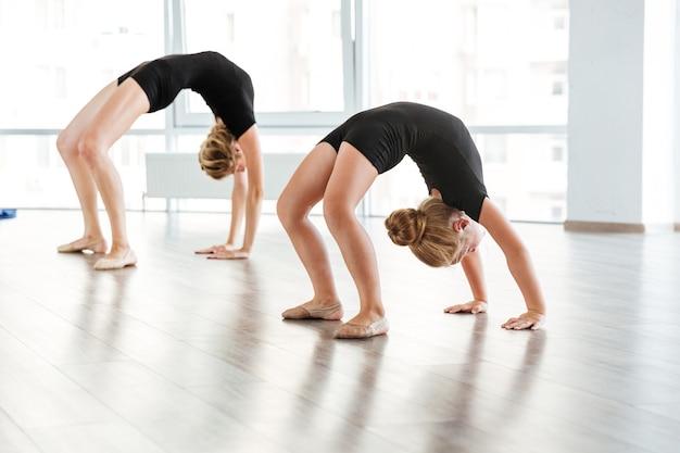Młody nauczyciel baletu i jej mały uczeń w studiu baletowym