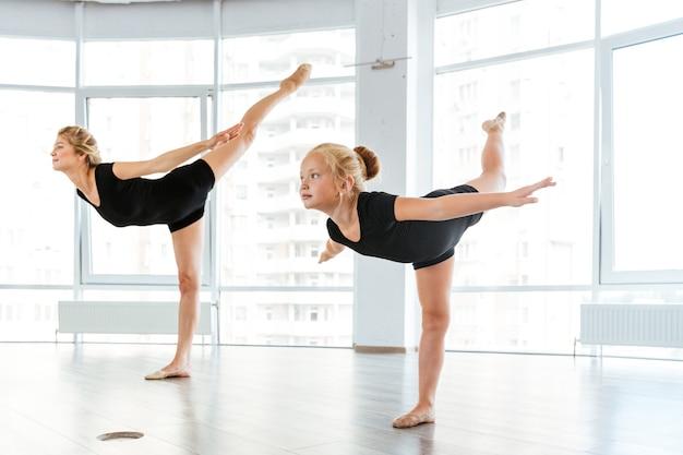 Młody nauczyciel baletu i jej mały uczeń w szkole baletowej