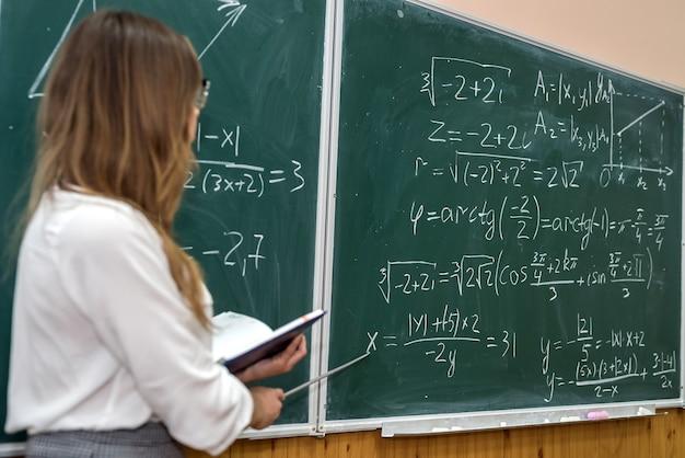 Młody nauczyciel college'u pisze ćwiczenia matematyczne na tablicy podczas zajęć. edukacja
