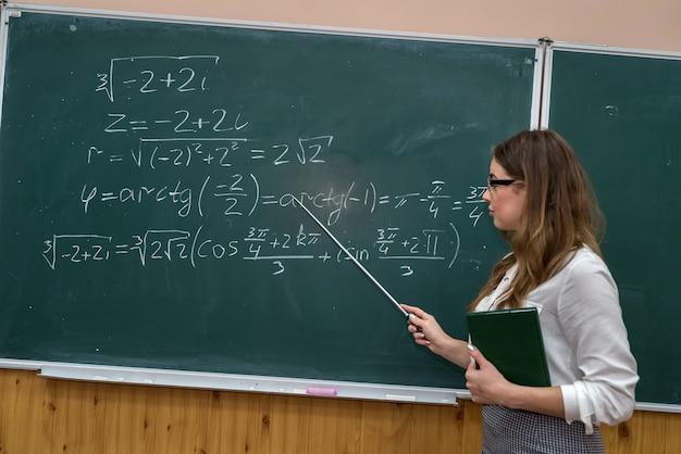 Młody nauczyciel piszący i wyjaśniający wzory matematyczne na tablicy szkolnej. edukacja