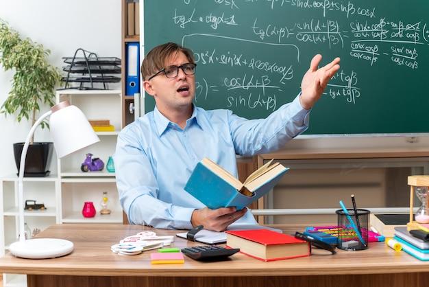 Młody nauczyciel płci męskiej w okularach, odsuwający się na bok, zdezorientowany i niezadowolony, podnosząc rękę z oburzeniem, siedząc w szkolnej ławce z książkami i notatkami przed tablicą w klasie