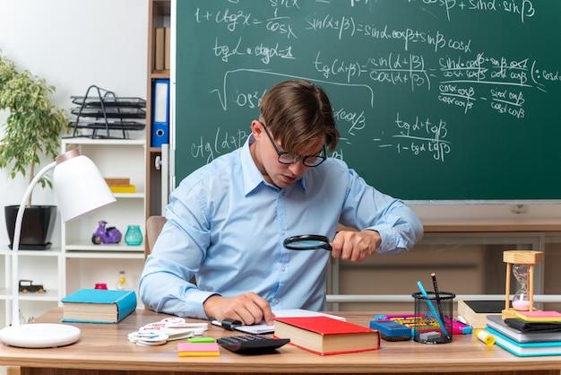 Młody nauczyciel płci męskiej w okularach, patrząc na notatki przez szkło powiększające, przygotowujący lekcję, siedząc przy ławce szkolnej z książkami i notatkami przed tablicą w klasie