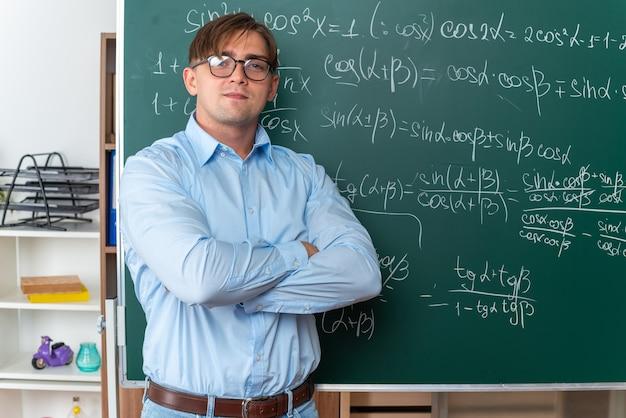 Młody nauczyciel płci męskiej w okularach, patrzący z pewnym siebie uśmiechem na twarzy z rękami skrzyżowanymi, stojący w pobliżu tablicy z formułami matematycznymi w klasie