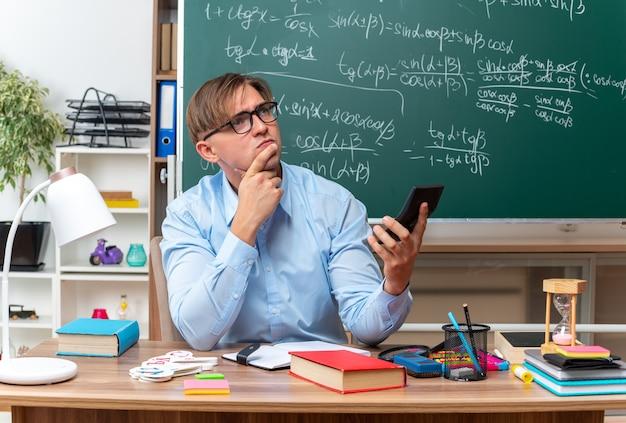 Młody nauczyciel płci męskiej w okularach, pisząc wiadomość za pomocą smartfona, patrząc zdziwiony, siedząc w ławce szkolnej z książkami i notatkami przed tablicą w klasie