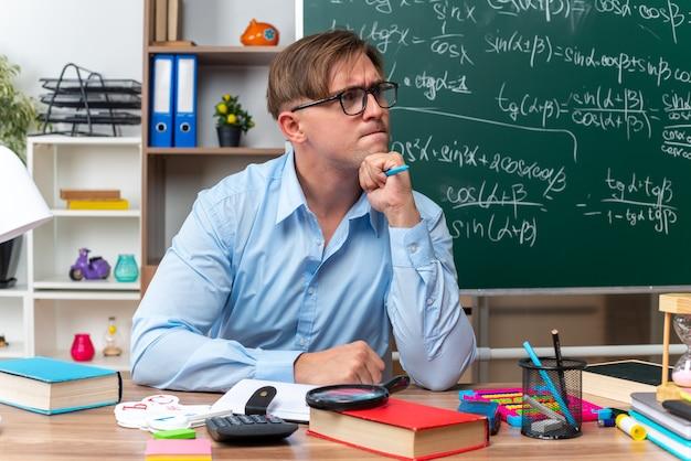 Młody nauczyciel płci męskiej w okularach siedzi przy ławce szkolnej z książkami i notatkami, patrząc na bok z zamyślonym wyrazem twarzy, myśląc przed tablicą w klasie