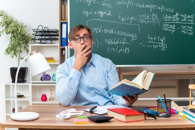 Młody nauczyciel płci męskiej w okularach trzymający książkę zszokowaną zakrywającą usta ręką siedzącą przy szkolnym biurku z książkami i notatkami przed tablicą w klasie