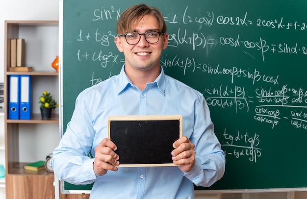 Młody nauczyciel płci męskiej w okularach trzymający małą tablicę, patrzący uśmiechnięty, pewnie stojący w pobliżu tablicy z formułami matematycznymi w klasie