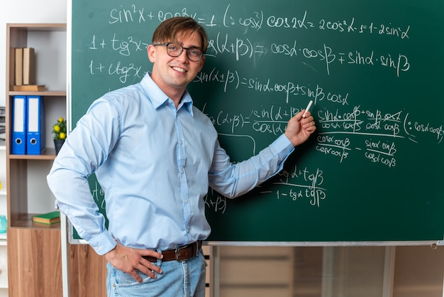 Młody nauczyciel płci męskiej w okularach trzymających kredę wyjaśniającą lekcję stojącą w pobliżu tablicy z formułami matematycznymi w klasie