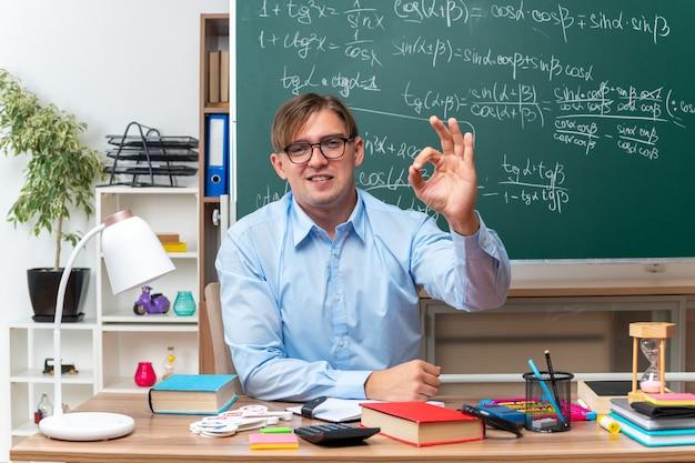 Młody nauczyciel płci męskiej w okularach uśmiechający się pewnie pokazując znak ok, siedzący przy ławce szkolnej z książkami i notatkami przed tablicą w klasie
