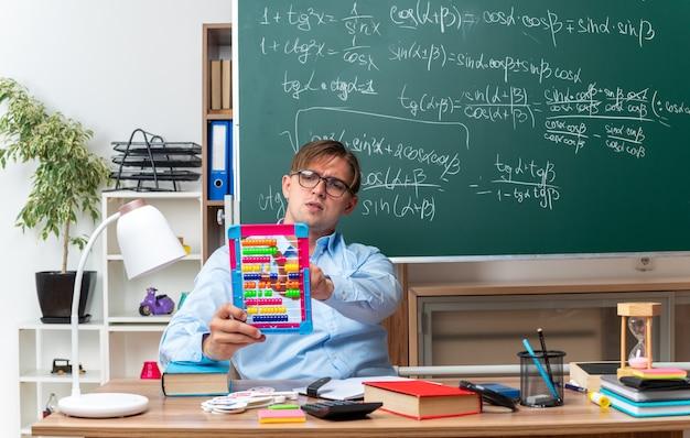 Młody nauczyciel płci męskiej w okularach z rachunkami wyglądający pewnie przygotowując lekcję, siedząc przy ławce szkolnej z książkami i notatkami przed tablicą w klasie