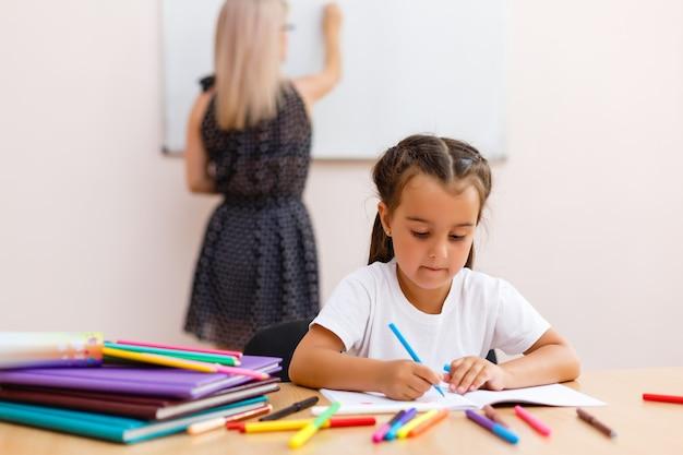 Młody nauczyciel przedszkola uczy małe dziewczynki w klasie
