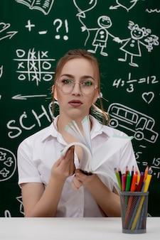 Młody nauczyciel siedzi w pobliżu tablicy w klasie