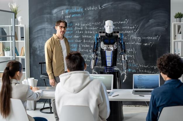 Młody nauczyciel stoi przy tablicy przed publicznością i przedstawia robota grupie uczniów na lekcji