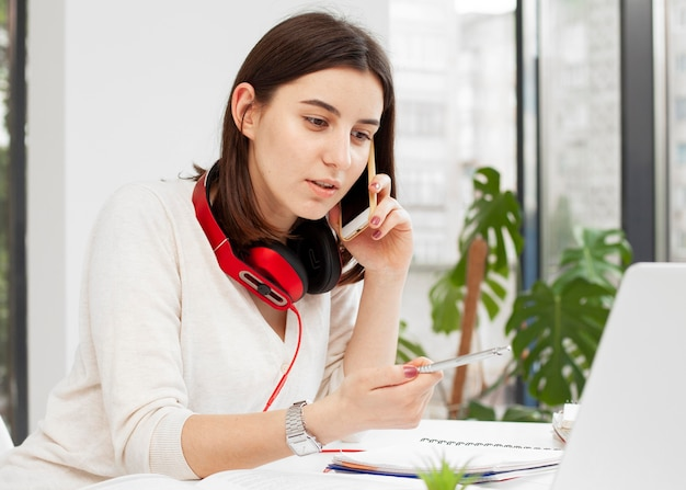Młody nauczyciel w domu rozmawia przez telefon