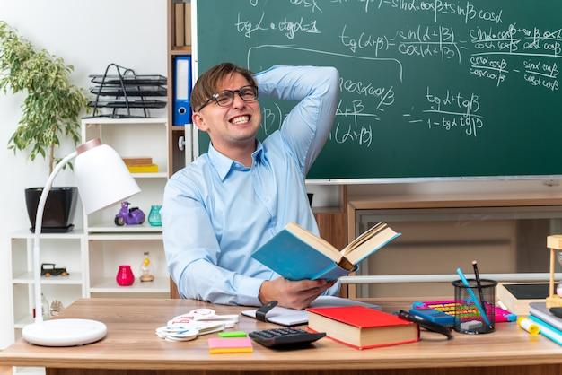 Młody nauczyciel w okularach loking zdezorientowany i rozczarowany, siedzący przy szkolnej ławce z książkami i notatkami przed tablicą w klasie