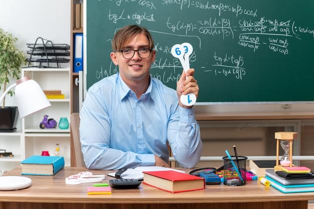 Młody nauczyciel w okularach pokazujący tablice rejestracyjne wyjaśniający lekcję uśmiechający się, siedzący przy ławce szkolnej z książkami i notatkami przed tablicą w klasie