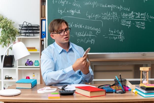 Młody nauczyciel w okularach przygotowujący lekcję wygląda pewnie siedząc w szkolnej ławce z książkami i notatkami przed tablicą w klasie