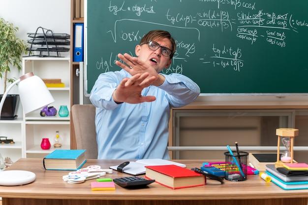Młody nauczyciel w okularach wyglądający na zmartwionego i zdezorientowanego, wykonujący gest obrony rękami siedzącymi przy ławce szkolnej z książkami i notatkami przed tablicą w klasie