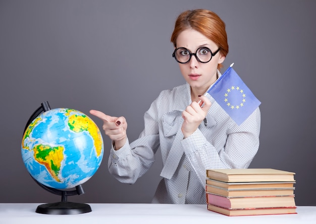 Młody nauczyciel w okularach z książkami, globusem i flagą unii europejskiej.